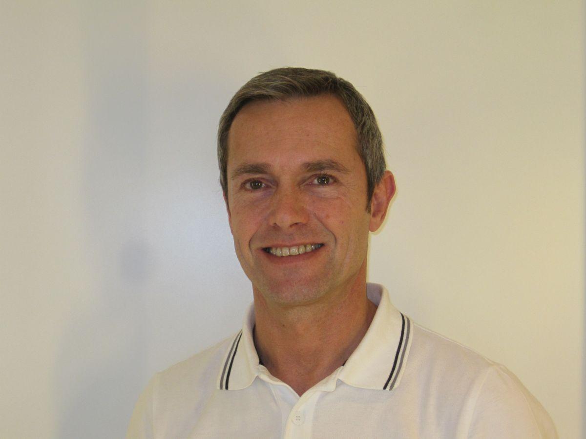 Das Foto zeigt Dieter Raggl aus Thalheim bei Wels vor einem hellen Hintergrund. Er hat kurzes dunkelgraues Haar und lächelt in die Kamera. Er trägt ein weißes Polo T-Shirt mit einem schwarzen Streifen am Kragen.