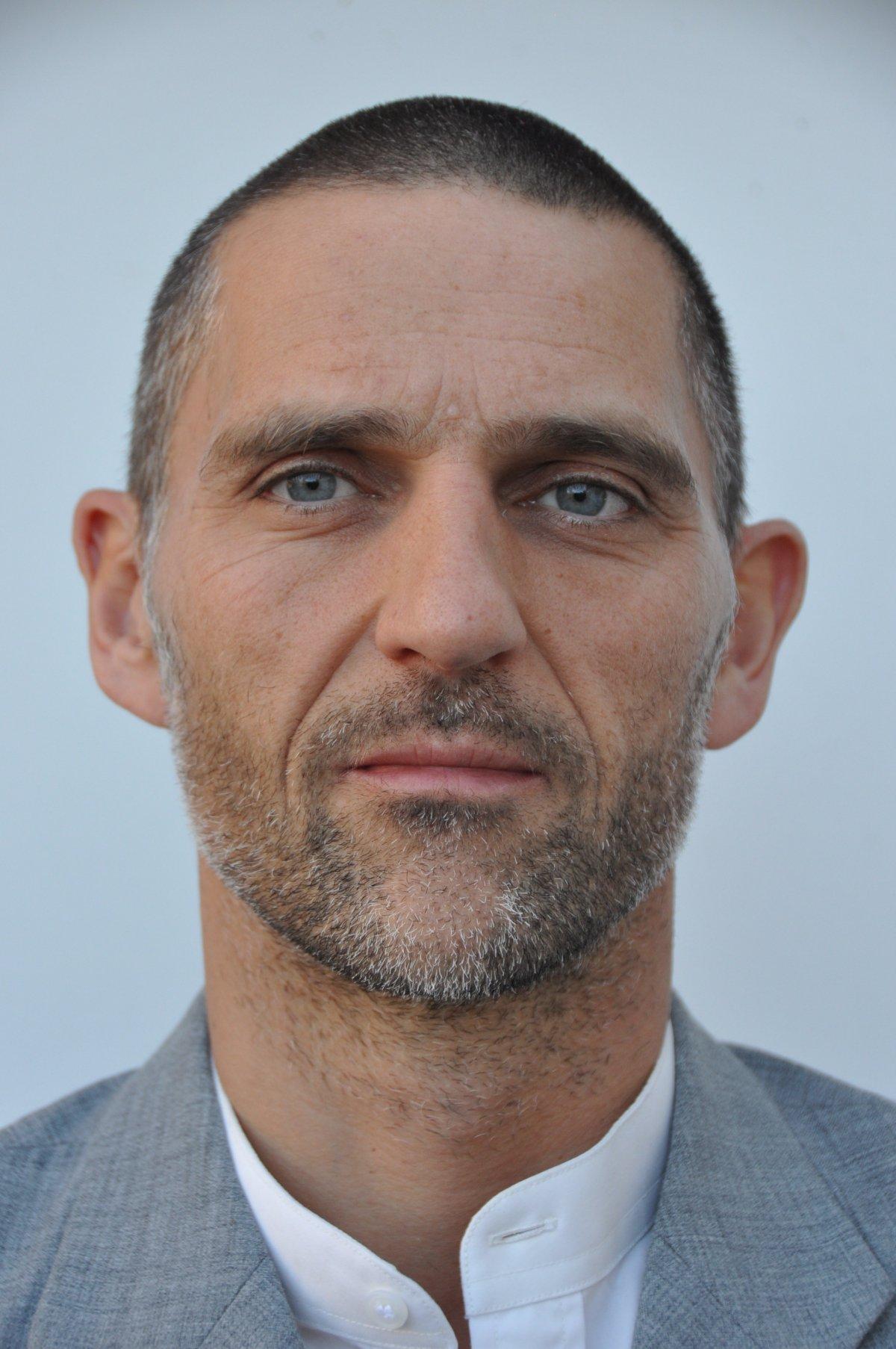 Auf dem Foto sieht man Dirk Lemke, der in Waldkirch behandelt. Er steht vor einem hellen Hintergrund. Er hat kurze schwarze Haare und einen schwarz grauen Dreitagebart. Dazu trägt er ein weißes Hemd und ein graues Sakko.