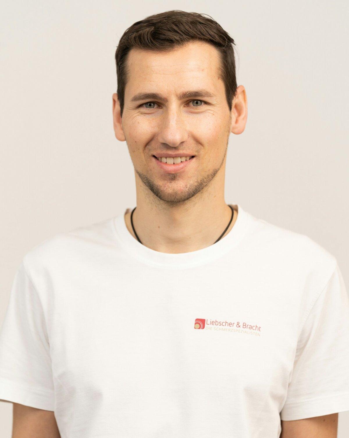 Der junge Physiotherapeut Dominic Bader hat braune Haare und einen Dreitagebart und steht mit einem weißen Liebscher & Bracht T-Shirt vor einem weißen Hintergrund.