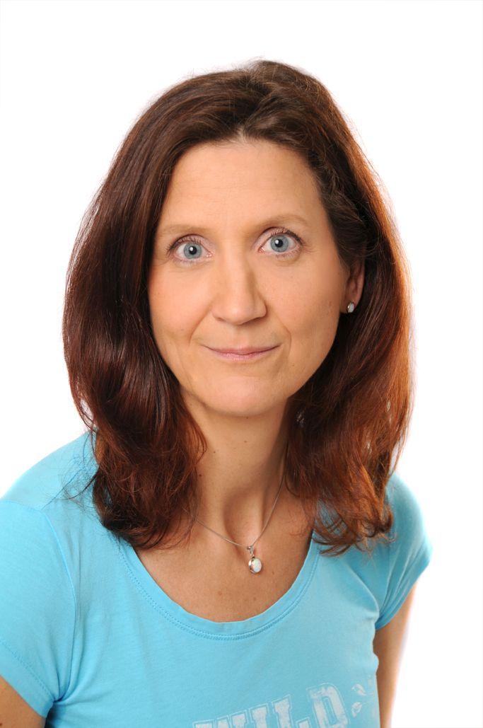 Das Foto zeigt Dorit Elsner aus Berlin. Sie hat schulterlange braune Haare, blaue Augen und trägt neben einer silbernen Kette ein türkisfarbenes T-Shirt.