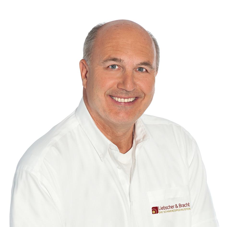 Dr. Markus Hundhammer ist Schmerztherapeut aus Grünwald. Er lächelt sympathisch, trägt ein weißes Liebscher & Bracht Hemd und hat eine Halbglatze mit grauen Haaren.