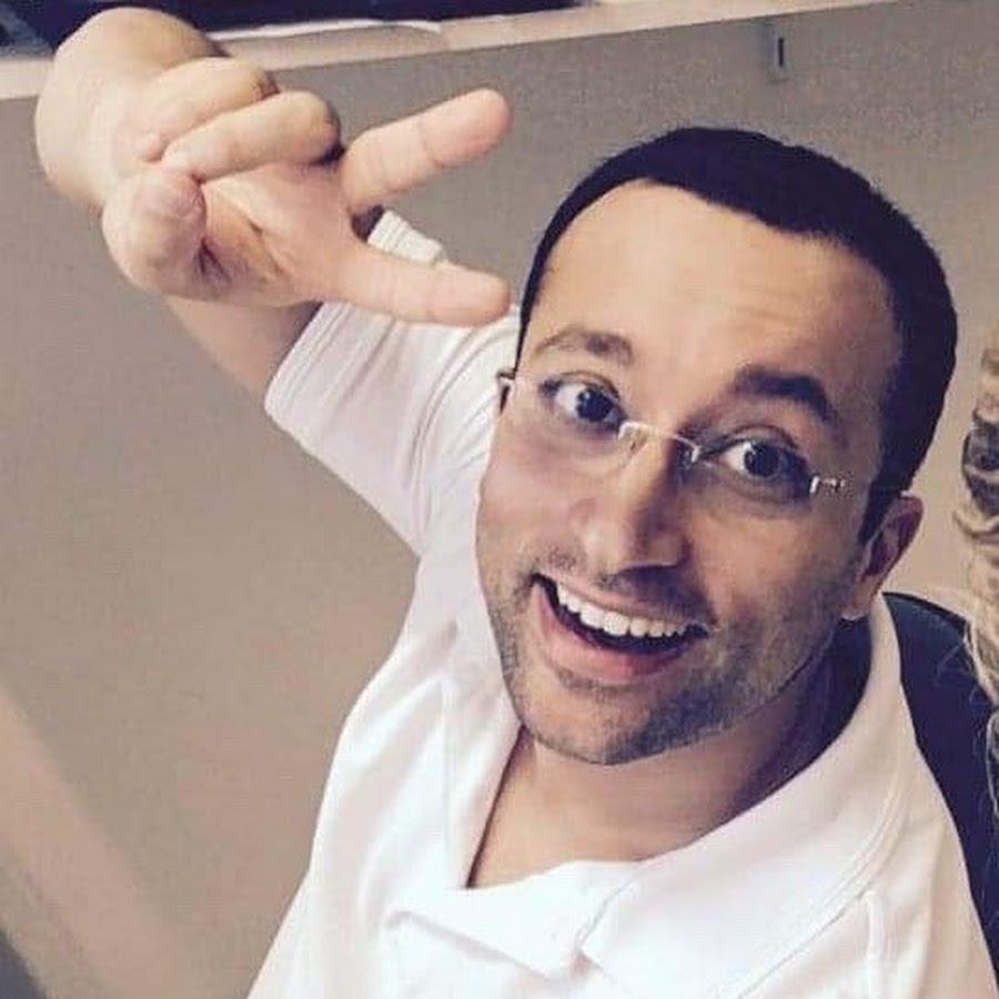 Dr. med. Arman Edalatpour sitzt auf einem Stuhl und schaut schräg nach oben in die Kamera. Er lacht und hält dabei die Finger als Peace-Zeichen in die Kamera. Außerdem trägt er ein weißes Polo T-Shirt und kurze schwarze Haare.