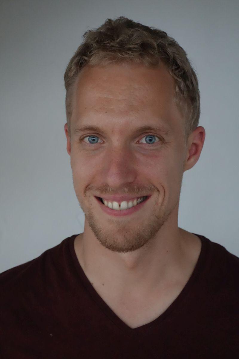Das Foto zeigt den Arzt Dr. med. Jan Kastell aus Heidelberg. Er hat blaue Augen und dunkelblonde Haare. Er hat einen Dreitagebart und trägt ein schwarzes T-Shirt.