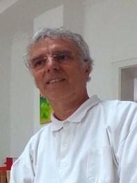 Das Foto zeigt Dr. Philipp Veith, welcher in Jever die Liebscher & Bracht Schmerztherapie praktiziert. Er trägt ein weißes Polo T-Shirt und eine randlose Brille. Er hat kurzes lockiges graues Haar.