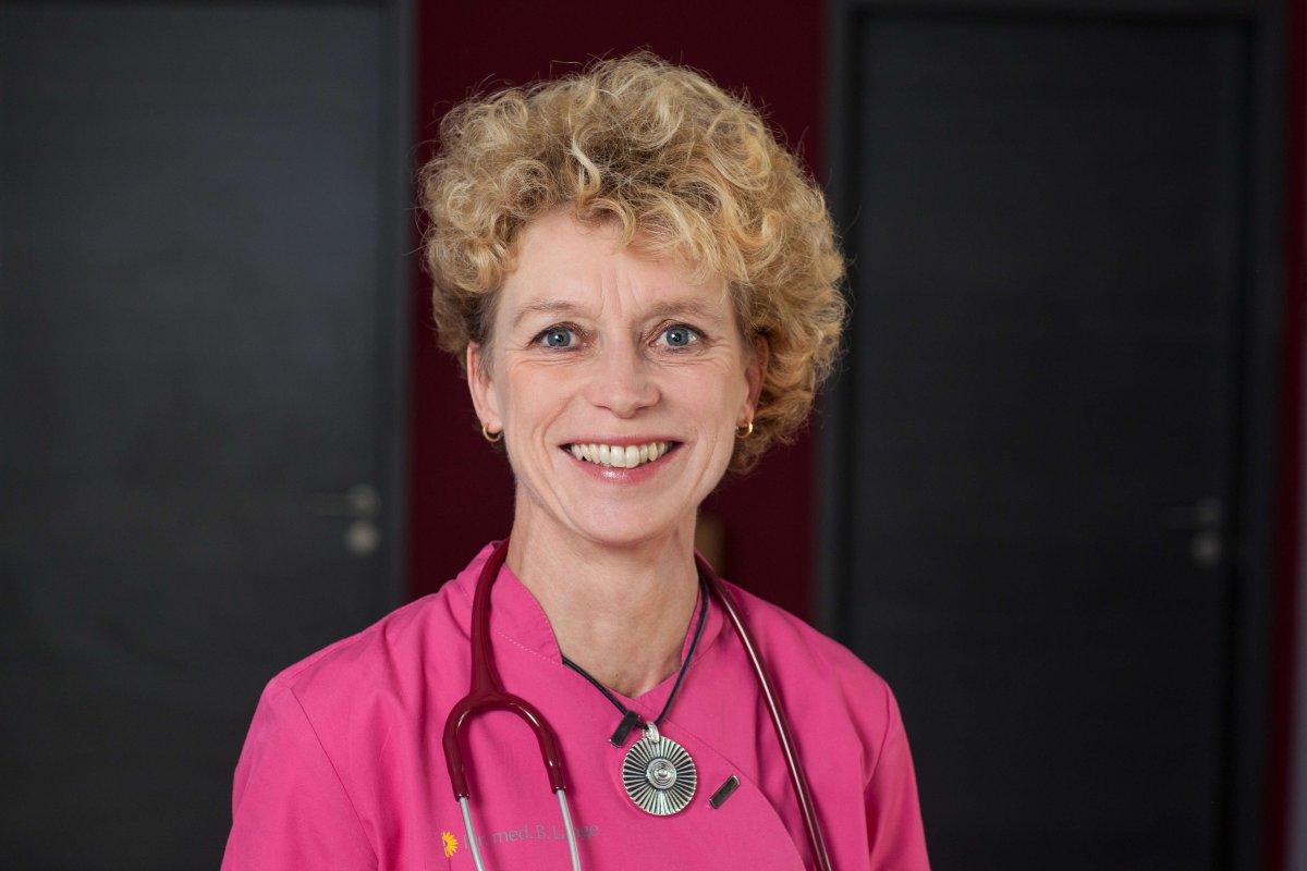 Das Foto zeigt die Fachärztin für Allgemeinmedizin und Naturheilverfahren aus Bad Berka. Dr. med. Bettina Lange hat kurze lockige blonde Haare und trägt auf dem Foto ein pinkes T-Shirt. Sie lächelt in die Kamera und hat ein rotes Stethoskop, sowie eine Ke