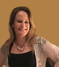 Das Foto wurde vor einer dunkelgelben Wand aufgenommen. Eveline Eppensteiner hat lange hellbraune Haare und trägt neben einem schwarzen T-Shirt eine helle Strickjacke und eine silberne Kette.