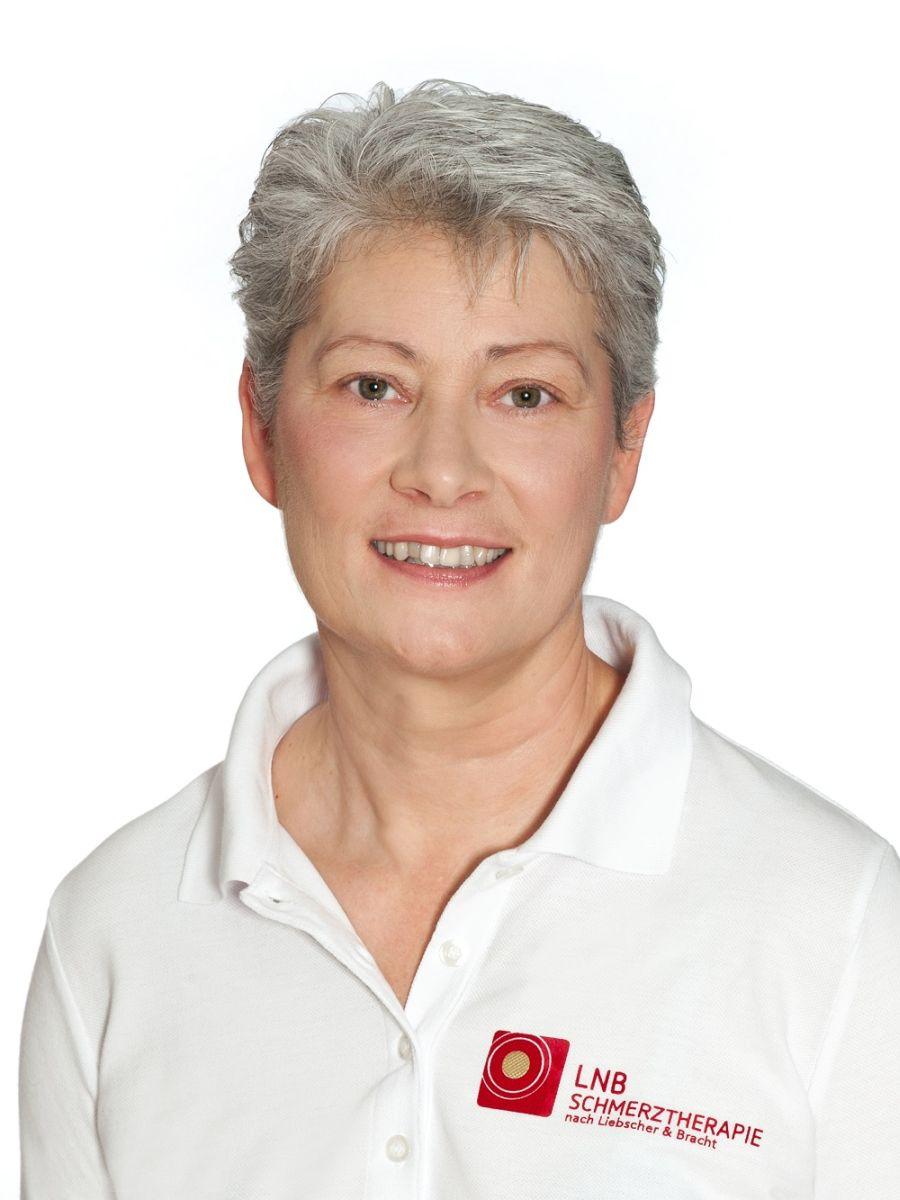 Das Bild zeigt Gabriele Jäger-Lindenberger vor einem weißen Hintergrund. Sie hat kurze graue Haare und trägt ein weißes Liebscher & Bracht Polo T-Shirt.