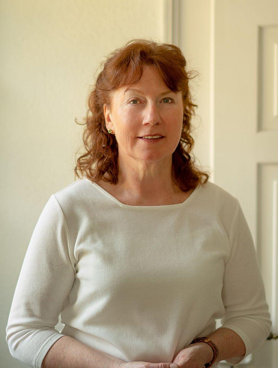 Das Foto zeigt Gabriele Lankoff vor einem hellen Hintergrund. Sie hat schulterlange braune Haare, die sich locken und einen Pony. Auf dem Bild trägt sie einen weißen Pullover.