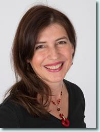 Das Portraitfoto der Schmerz- und Bewegungstherapeutin Daniela Haller aus Zürich-Enge zeigt sie lächelnd vor einem weißen Hintergrund. Sie hat lange braune Haare und trägt eine rote Kette.