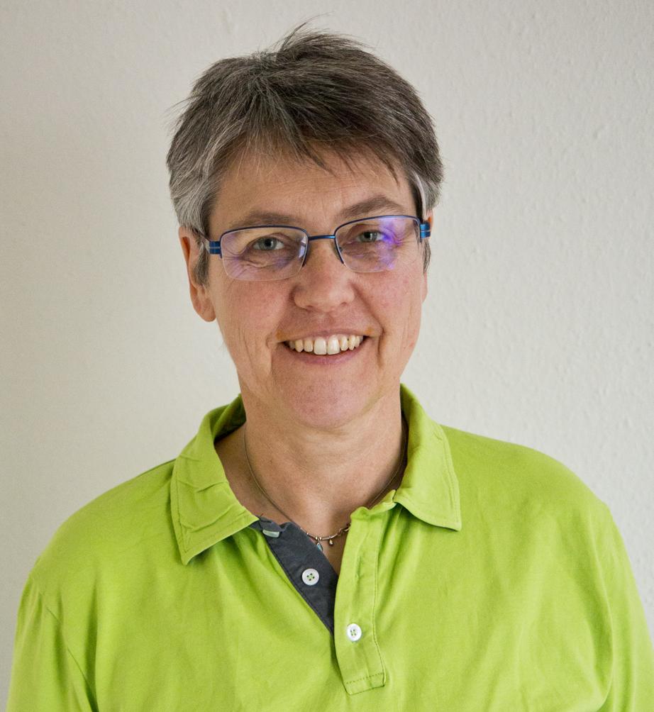 Hanna Müller-Jäckel wurde vor einem weißen Hintergrund fotografiert. Sie hat kurze dunkelgraue Haare und trägt eine eckige Brille sowie ein grünes Polo T-Shirt.