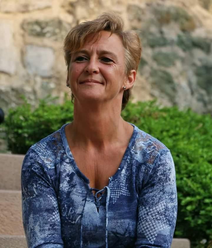 Das Foto zeigt Hedwig Miszka aus Lich vor einem Hintergrund mit Steinen und grünem Gebüsch. Sie lächelt und schaut nicht direkt in die Kamera. Auf dem Foto hat sie kurze hellbraune Haare und trägt eine blaue gemusterte Bluse.