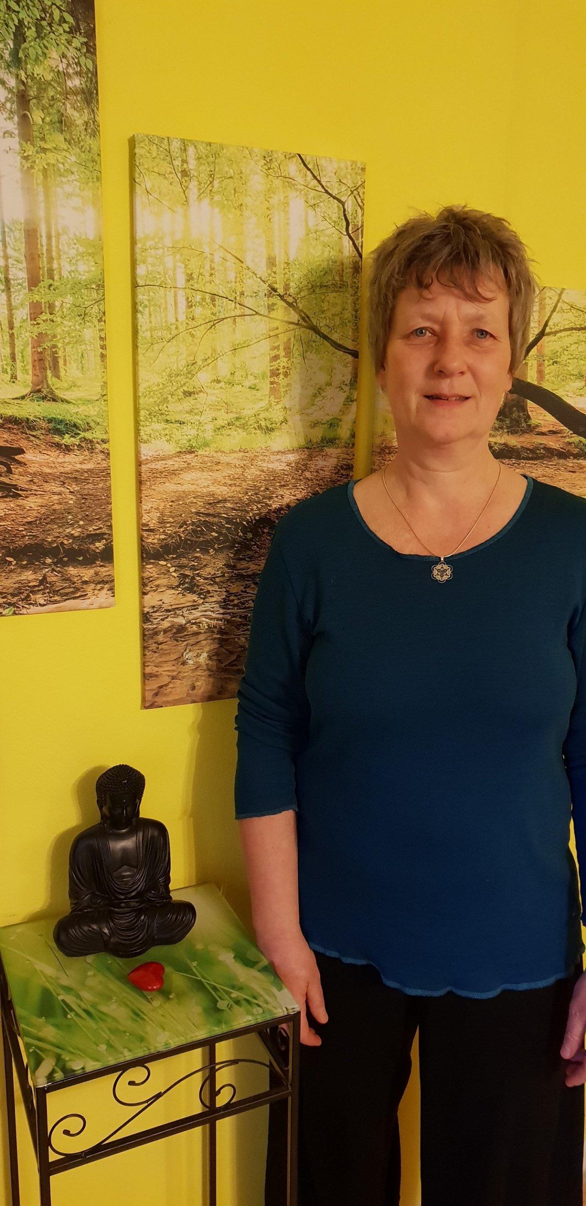 Das Foto zeigt Heike Pedinna vor einem gelben Hintergrund mit Bildern aus dem Wald. Links neben ihr steht ein kleiner Tisch mit einer Buddhafigur und einem roten Herz drauf. Sie hat kurze dunkelblonde Haare und trägt neben einem dunkelblauen Shirt eine sc