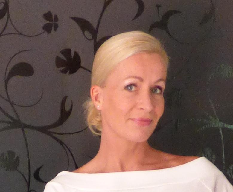 Das Foto zeigt die lächelnde Heike Schlauch-Wacker aus 71540 Murrhardt vor einem schwarzen Hintergrund mit Mustern. Sie hat blonde Haare, die sie als Zopf trägt. Auf dem Foto trägt sie ein weißes T-Shirt.