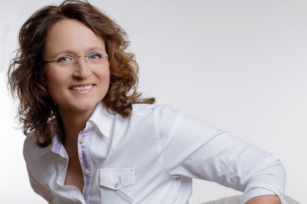 Heike Wright ist vor einem weißen Hintergrund fotografiert. Sie hat schulterlange braune lockige Haare und eine rahmenlose Brille. Auf dem Foto trägt sie eine weiße Bluse.