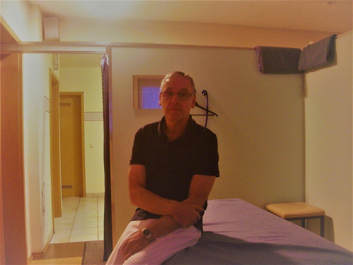 Das Foto zeigt Helmut Nitschke aus 84547 Emmerting seitliche sitzend auf einer Behandlungsbank. Er hat die Arme vor dem Körper verschränkt. Er hat kurze graue Haare, trägt eine Brille und ein dunkles Polo T-Shirt sowie eine weiße Hose.