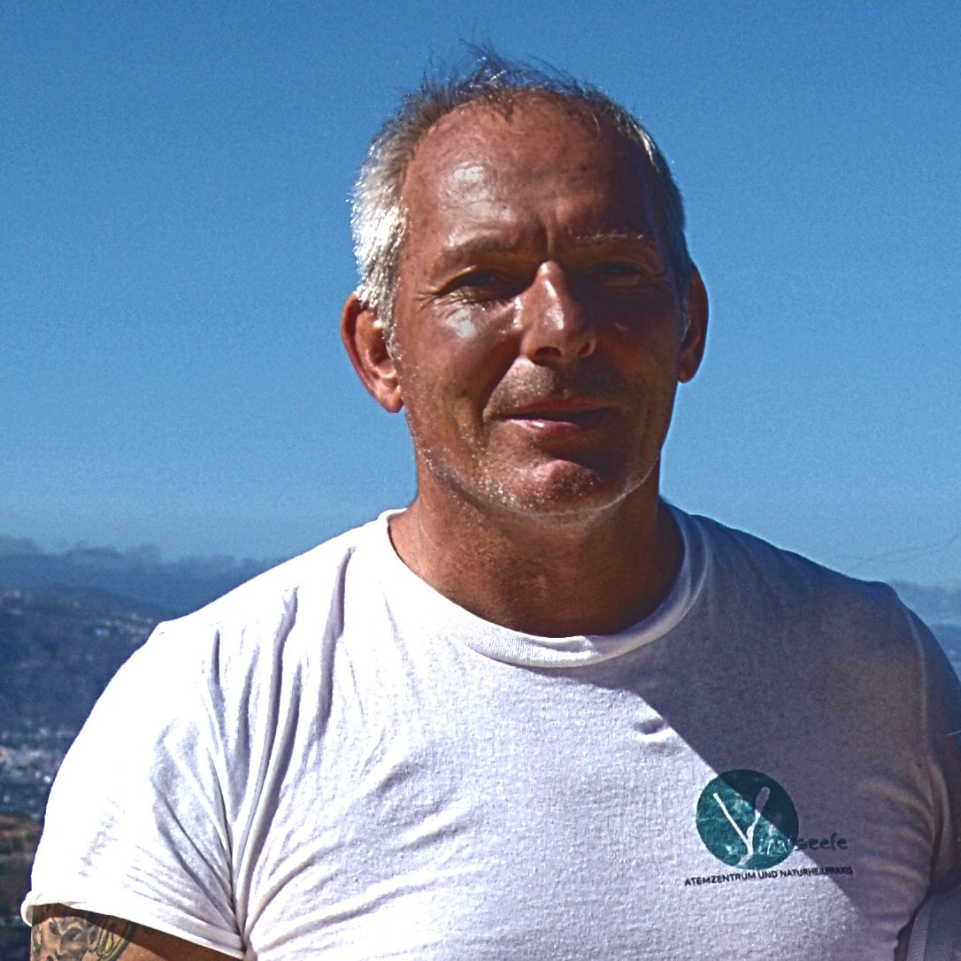 Das Foto zeigt Helmut Pfeil aus 6780 Schruns. Er steht vor einer blauen Kulisse und von der Seite scheint ihn die Sonne an. Er hat eine Halbglatze mit kurzem grauen Haar und trägt ein weißes T-Shirt mit einem Aufdruck.