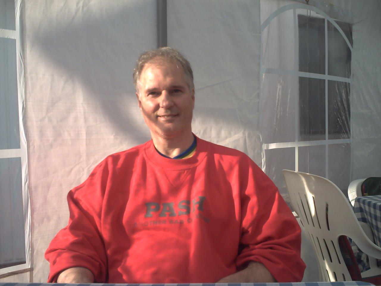 Auf dem Foto steht Herbert Amare Degu vor einer weiten Landschaft mit Häusern. Er hat kurzes graues Haar und trägt eine Sonnenbrille. Außerdem trägt er einen grauen Pullover.