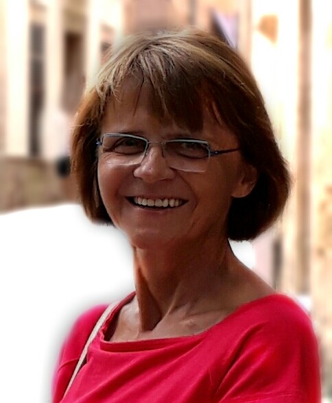 Das Foto zeigt Hildegard Binder aus Berlin vor einem hellen Hintergrund. Sie hat kinnlange braune Haare und einen geraden Pony und trägt eine eckige Brille sowie ein rotes Shirt.