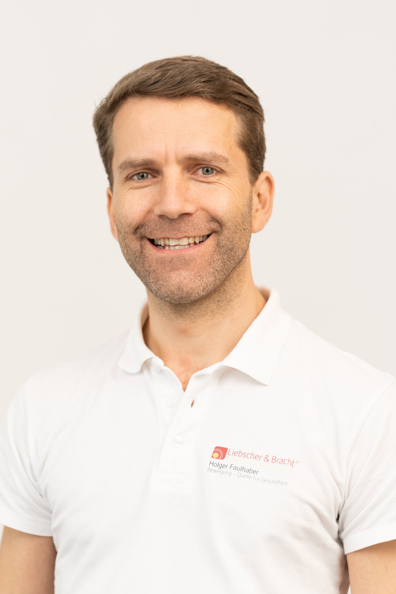 Schmerzspezialist Holger Faulhaber steht lächelnd vor einem dunkelgrauen Hintergrund. Er trägt ein türkisfarbenes T-Shirt und eine hellbraune eckige Brille.