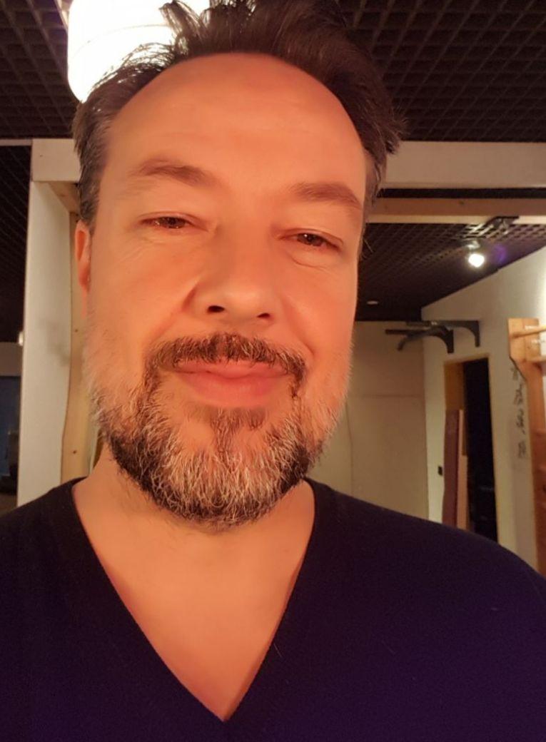 Auf dem Bild ist Marco Rösler aus Oldenburg abgebildet. Er hat kurze braune Haare und einen braun-grauen Vollbart. Auf dem Bild trägt er einen schwarzen Pullover.