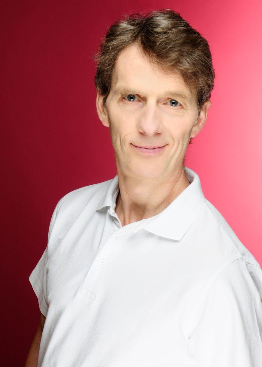 Auf dem Foto steht Hubert Brüderlein vor einem roten Hintergrund. Er hat kurzes braunes leicht gewelltes Haar und trägt auf dem Foto ein weißes Polo T-Shirt und lächelt in die Kamera.