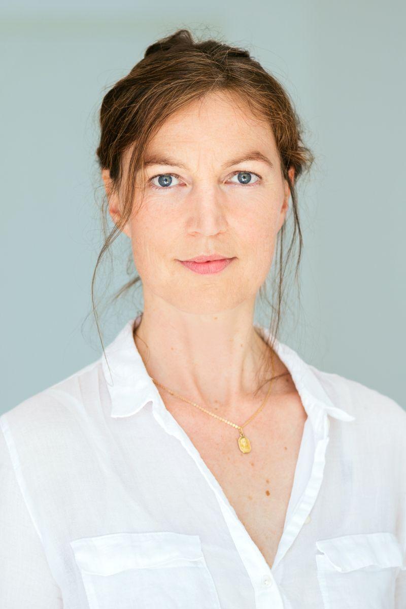 Die Heilpraktikerin Ilke Haasper aus Köln schaut mit ihren blauen Augen gerade in die Kamera. Sie trägt ihre braunen Haare zu einem Zopf, wobei einzelne Strähnen herausfallen. Das Portraitfoto zeigt sie vor einem hellgrauen Hintergrund und mit einer weiße