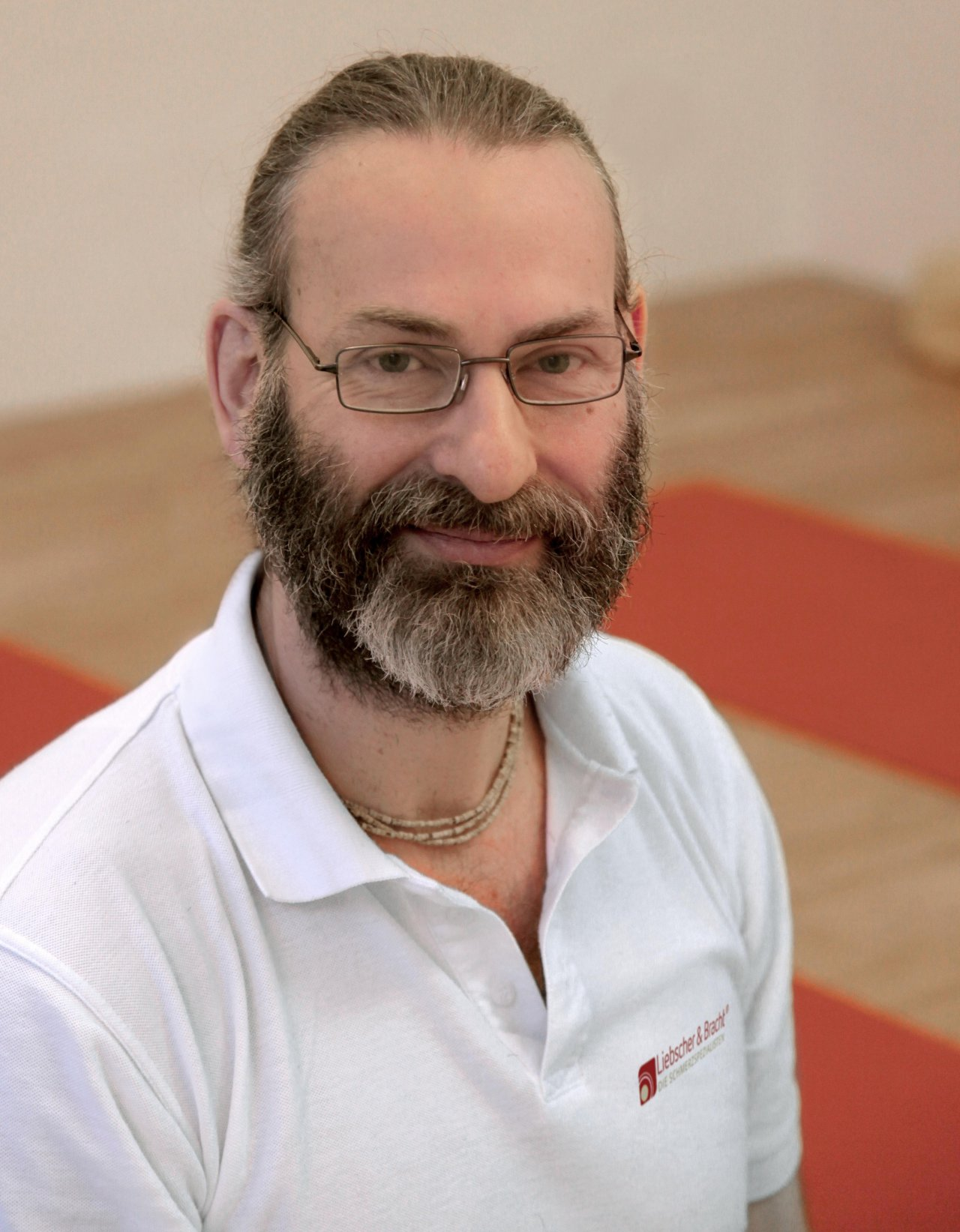 Ingo Mende aus Berlin schaut schräg nach oben in die Kamera. Er hat lange schwarz graue Haare, die er als Zopf trägt und einen dicken Vollbart. Er trägt eine eckige Brille und eine hellbraune Brille sowie ein weißes Liebscher & Bracht Polo T-Shirt.