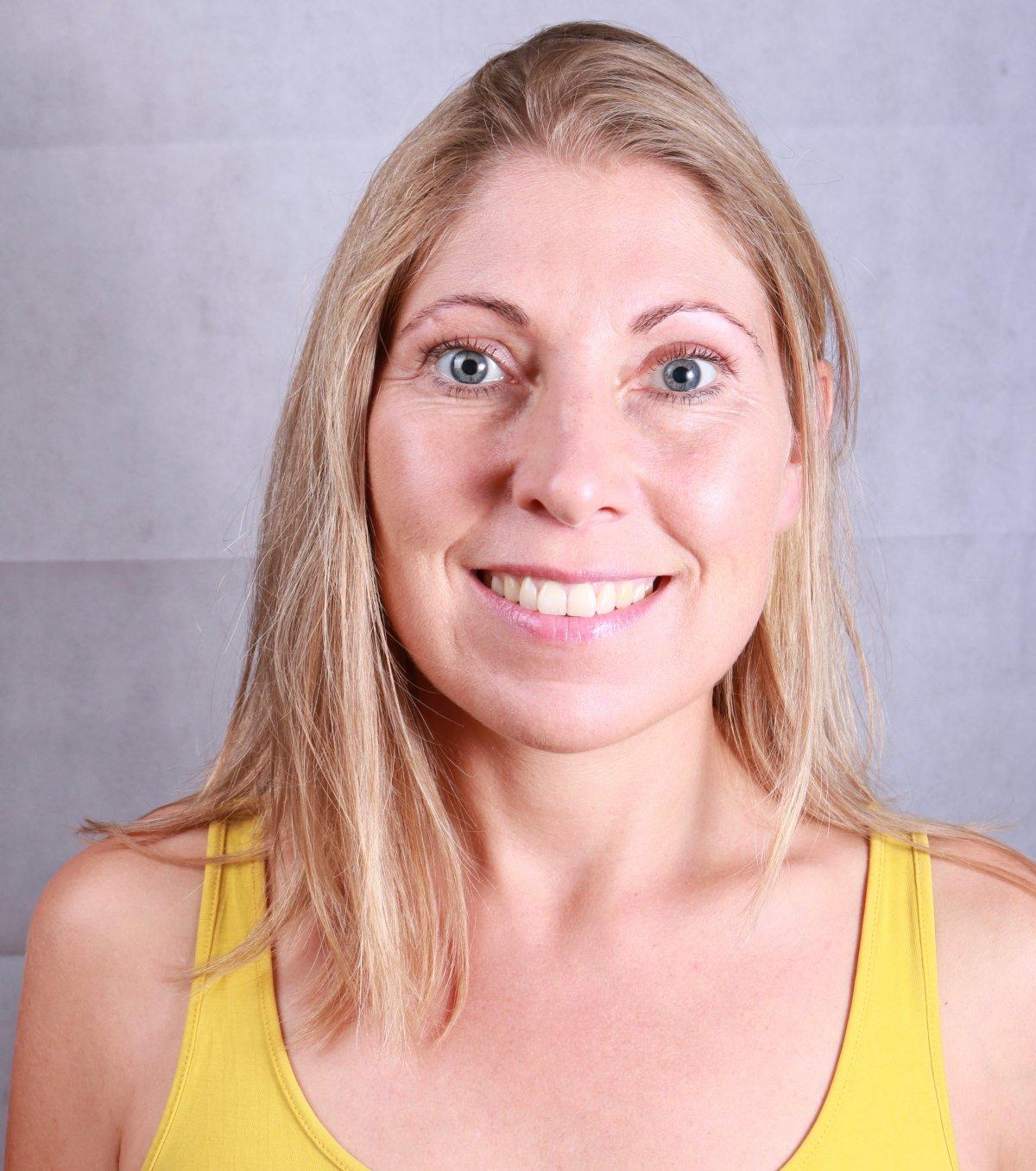 Auf dem Foto lacht Irene Bohmann aus Würzburg in die Kamera. Sie hat lange blonde Haare und trägt ein gelbes Top.