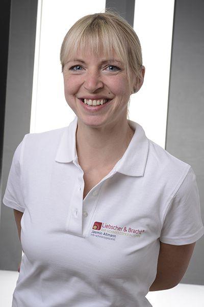 Liebscher & Bracht Schmerztherapeutin Jasmin Altmann hat einen blonden Pony und trägt die Haare in einem Zopf. Auf dem Foto steht sie in einem weißen Liebscher & Bracht Polo T-Shirt vor einem hellen Hintergrund.