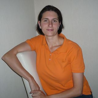 Das Foto zeigt Jessica Meyer aus Delmenhorst auf seitlich auf einem Stuhl sitzend. Sie hat den einen Arm über die Stuhllehne gelegt. Ihre dunklen Haare trägt sie kinnlang und dazu trägt sie ein orangenes Polo T-Shirt.