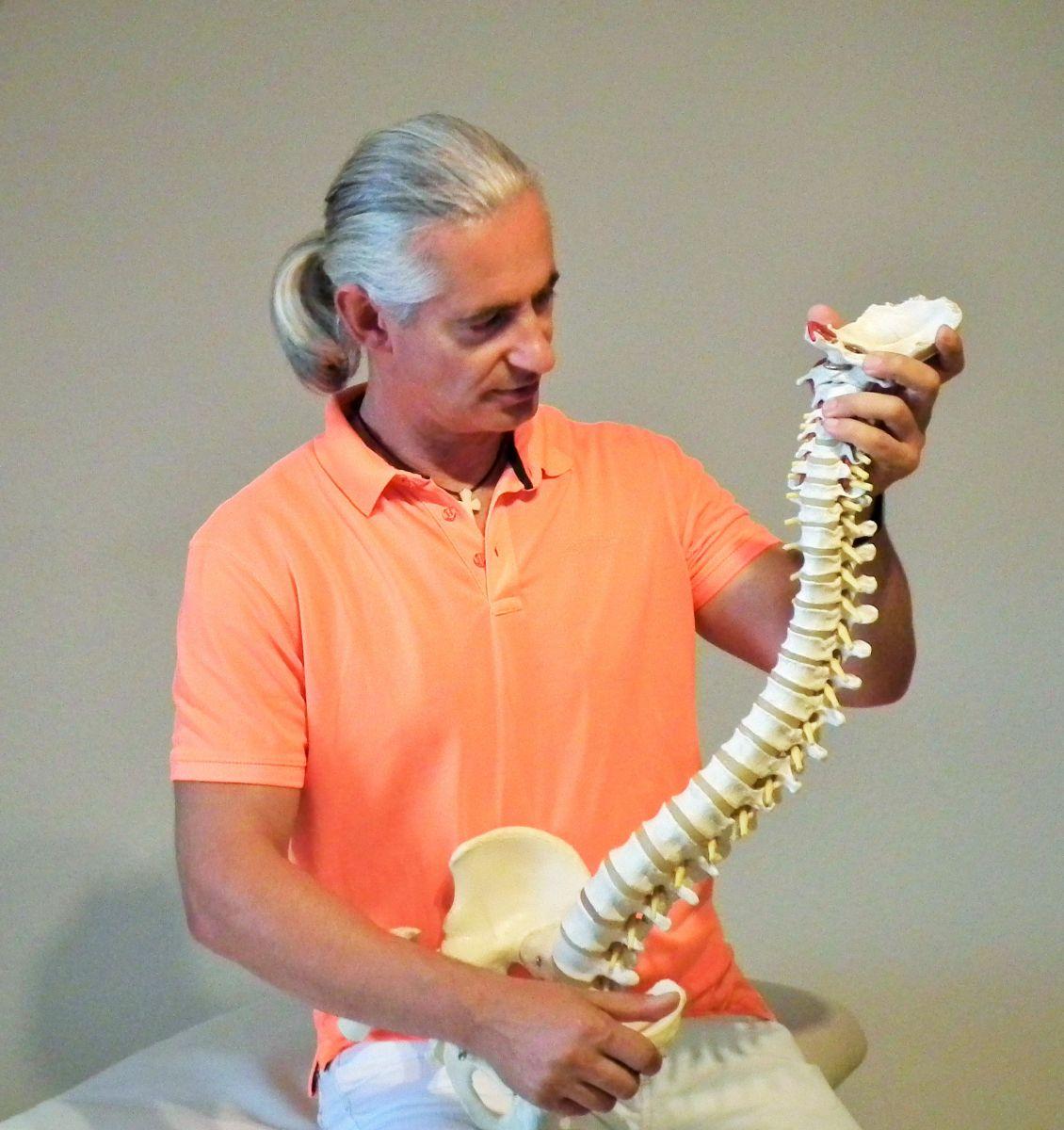 Auf dem Foto sitzt Joachim Richler auf einer Behandlungsbank und hält in seinen Händen ein Modellwirbelsäule. Er hat lange graue Haare, die er als Zopf gebunden hat und ein orangenes Polo T-Shirt. Er schaut auf die Wirbelsäule.