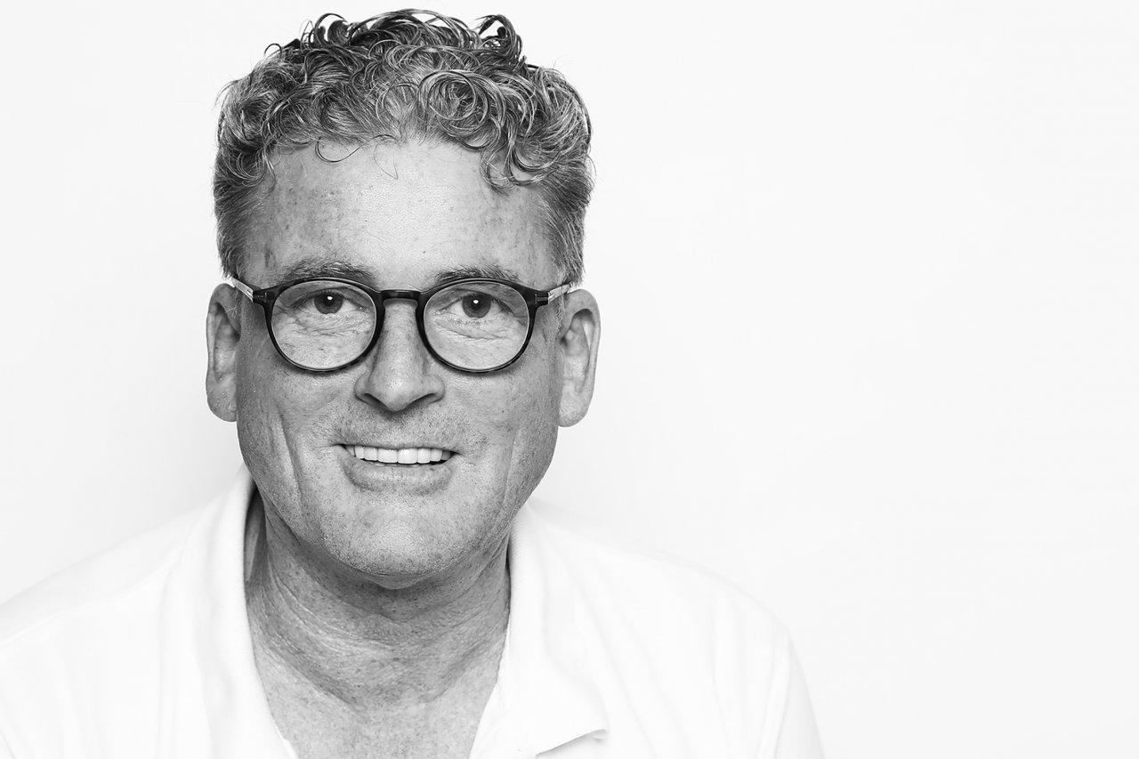 Das Foto zeigt Jürgen R. Hahn aus Reinbek. Der L& B Schmerzspezialist trägt ein weißes T-Shirt und längere Braun-graue Locken, die er nach hinten gebunden hat.