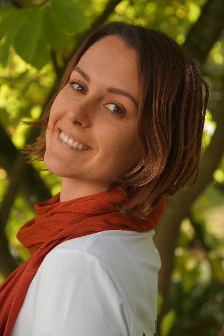 Auf dem Foto ist Julia Tröster vor einem grünen Naturhintergrund zu sehen. Sie hat kinnlange gestufte braune Haare und trägt ein rotes Tuch und ein weißes T-Shirt. Frau Tröster steht seitlich und schaut seitlich zur Kamera.