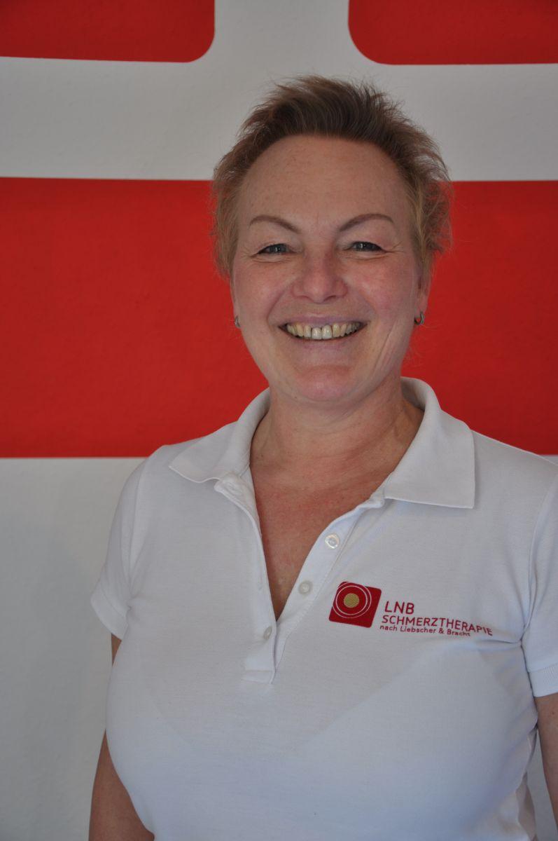Das Foto zeigt Jutta Feller aus 96515 Sonneberg vor einem rot weißen Hintergrund. Sie lacht in die Kamera. Auf dem Foto trägt sie kurze blonde Haare und ein weißes Liebscher & Bracht Polo T-Shirt.