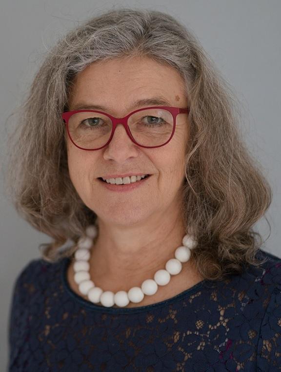 Das Foto zeigt Karin Krein aus 51465 Bergisch Gladbach. Sie hat schulterlange grau-braune Haare, die sich leicht locken. Sie trägt eine rote eckige Brille und eine weiße Perlenkette sowie ein blaues Shirt.