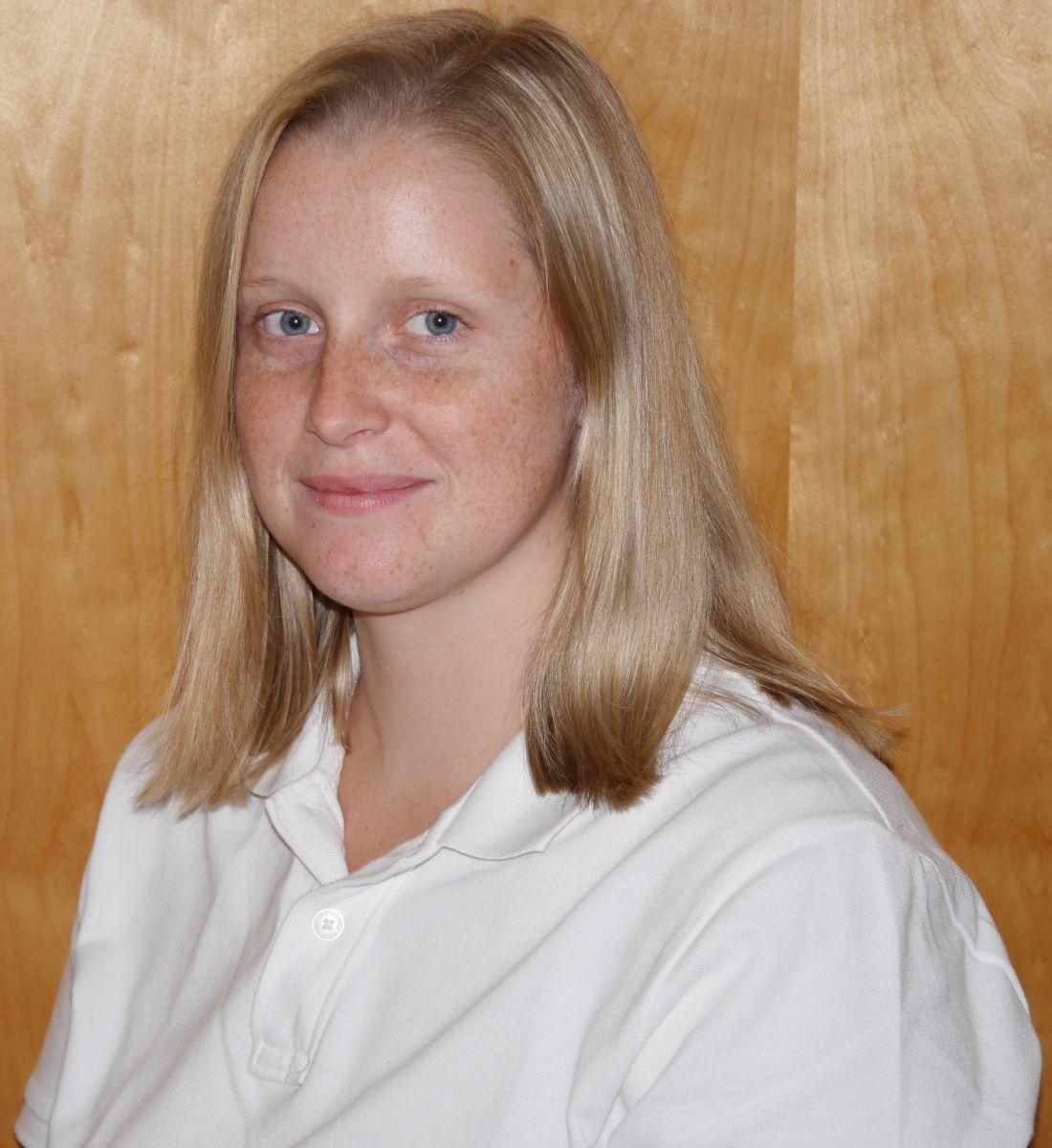 Das Foto zeigt Katharine Weigl aus Graz vor einer Holzwand. Sie hat schulterlange blonde Haare und viele Sommersprossen im Gesicht. Sie steht schräg zur Kamera und trägt ein weißes Polo T-Shirt.