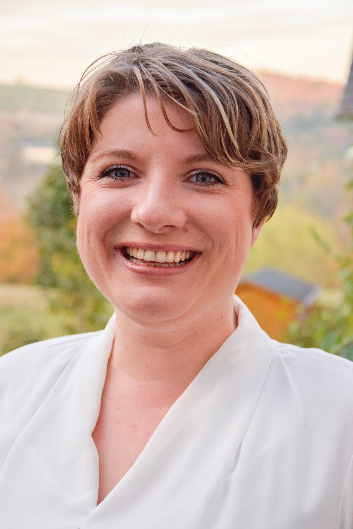 Das Foto zeigt die Physiotherapeutin Katrin Heindrichs aus Trier. Im Hintergrund sieht man Natur. Sie hat kurze braune Haare, lacht in die Kamera und trägt eine weiße Bluse.