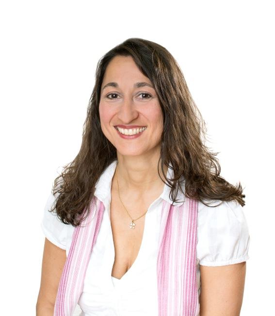 Das Foto zeigt Kyriakoula Topaloudis vor einem weißen Hintergrund. Sie hat lange braune Haare, die sich leicht wellen. Sie trägt eine weiße kurzärmlige Bluse und ein rosa Tuch sowie eine silberne Kette. Sie lacht in die Kamera.