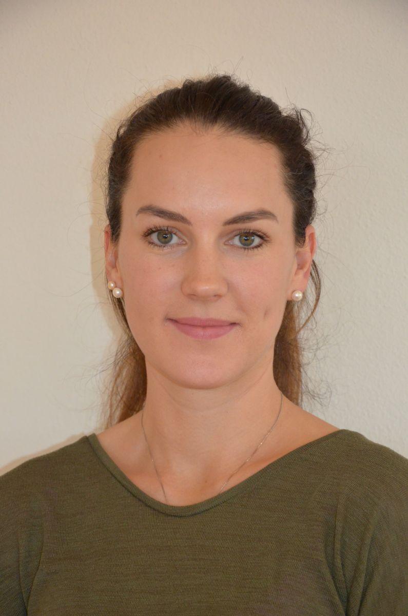 Das Portraitfoto zeigt Laura Hofinger aus 4600 Wels vor einem hellen Hintergrund. Sie trägt ihre langen braunen Haare als Zopf und ein khakifarbenes Oberteil sowie Perlenohrringe und eine silberne Kette.