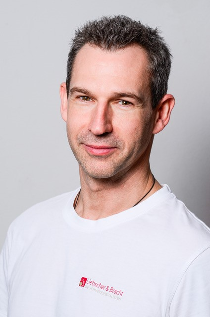 Oberkörper Bild von Stefan Lichtenstrasser mit dunklen Haaren und einem weißen Liebscher & Bracht T-Shirt vor einem weißen Hintergrund.