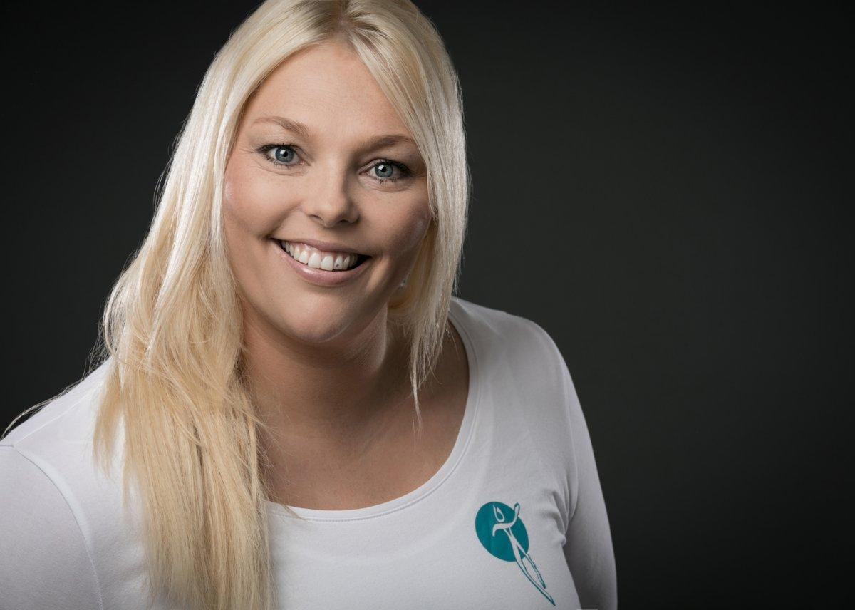 Das Foto zeigt Linda Freund aus Weilmünster vor einem schwarzen Hintergrund. Sie hat lange blonde Haare und lacht in die Kamera. Dazu trägt Sie ein weißes langes Shirt mit einem grünen Logo.