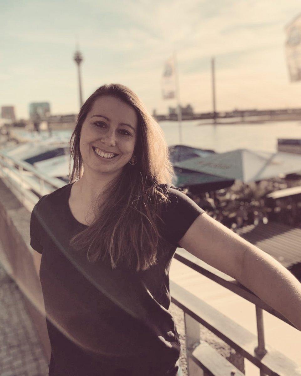 Das Foto zeigt Linda Jensen aus Velen. Im Hintergrund ist Wasser und ein Hafen zu erkennen. Sie hat lange braune Haare und trägt ein dunkles T-Shirt. Sie lehnt an einem Geländer und lacht herzlich in die Kamera.