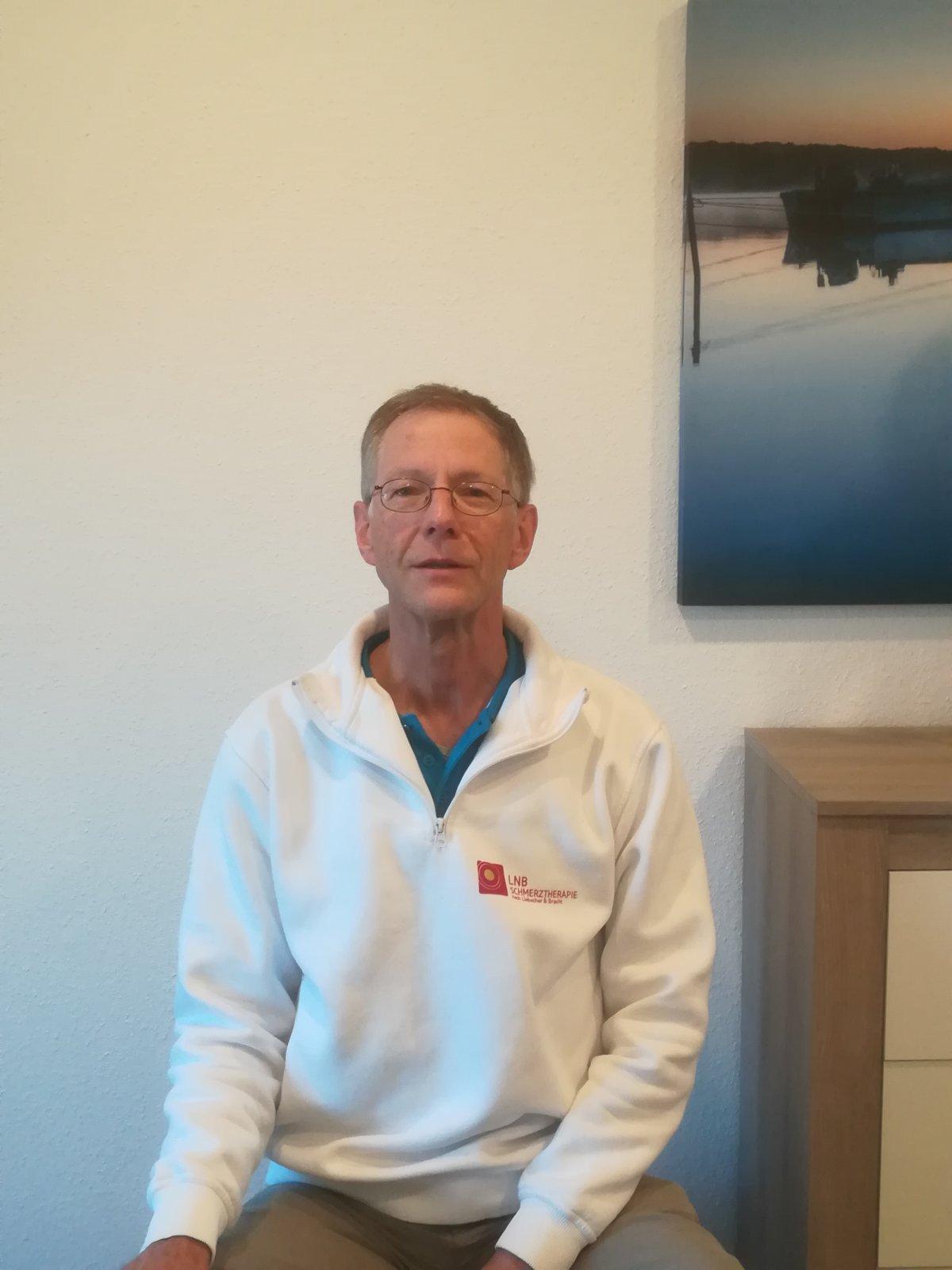 Das Bild zeigt Lothar Henk aus 26382 Wilhelmshaven. Er sitzt auf einem Stuhl vor einer hellen Wand. Am rechten Bildrand ist ein Bild und ein Regal zu erkennen. Lothar Henk hat hellgraues Haar und trägt eine eckige Brille. Auf dem Bild trägt er einen weiße
