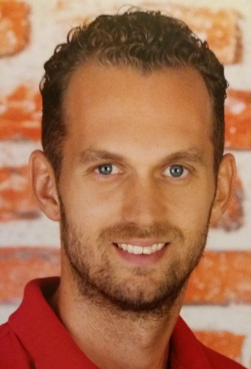 Auf dem Foto ist Lukas Mössner aus Hornstein vor einer roten Backsteinwand zu sehen. Er hat kurze braune Haare, die sich locken und einen Vollbart. Auf dem Bild trägt er ein rotes Polo T-Shirt.
