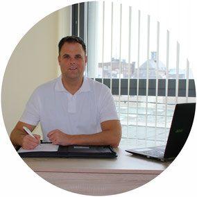 Auf dem runden Bildausschnitt ist M. Butzbach aus Neuss zu sehen. Er sitzt an einem Schreibtisch und unterschreibt ein Dokument während er freundlich in die Kamera schaut. Er hat kurze braune Haare und trägt ein weißes Polo T-Shirt.