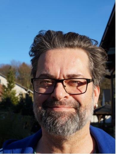 Auf dem Foto lächelt Marcus Kawe-Dreyer in die Kamera. Er hat kurze braune Haare und einen braun-grauen Vollbart. Er trägt einen Ohrring im linken Ohr und eine dunkle eckige Brille sowie ein blaues T-Shirt.