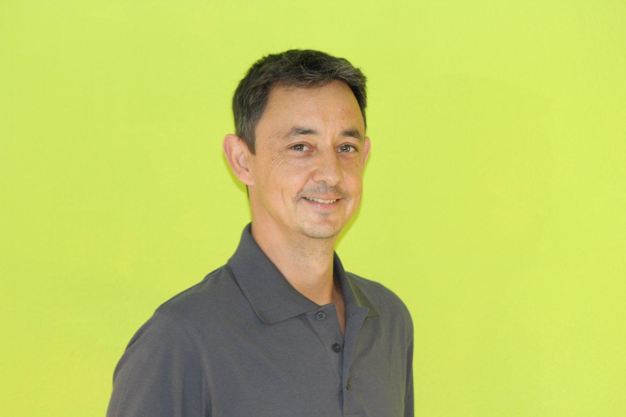 Das Foto zeigt den Physiotherapeuten Marek Geißler aus 30826 Garbsen. Er steht vor einem grünen Hintergrund und schaut direkt in die Kamera. Er hat kurze schwarze Haare und trägt ein graues Hemd.