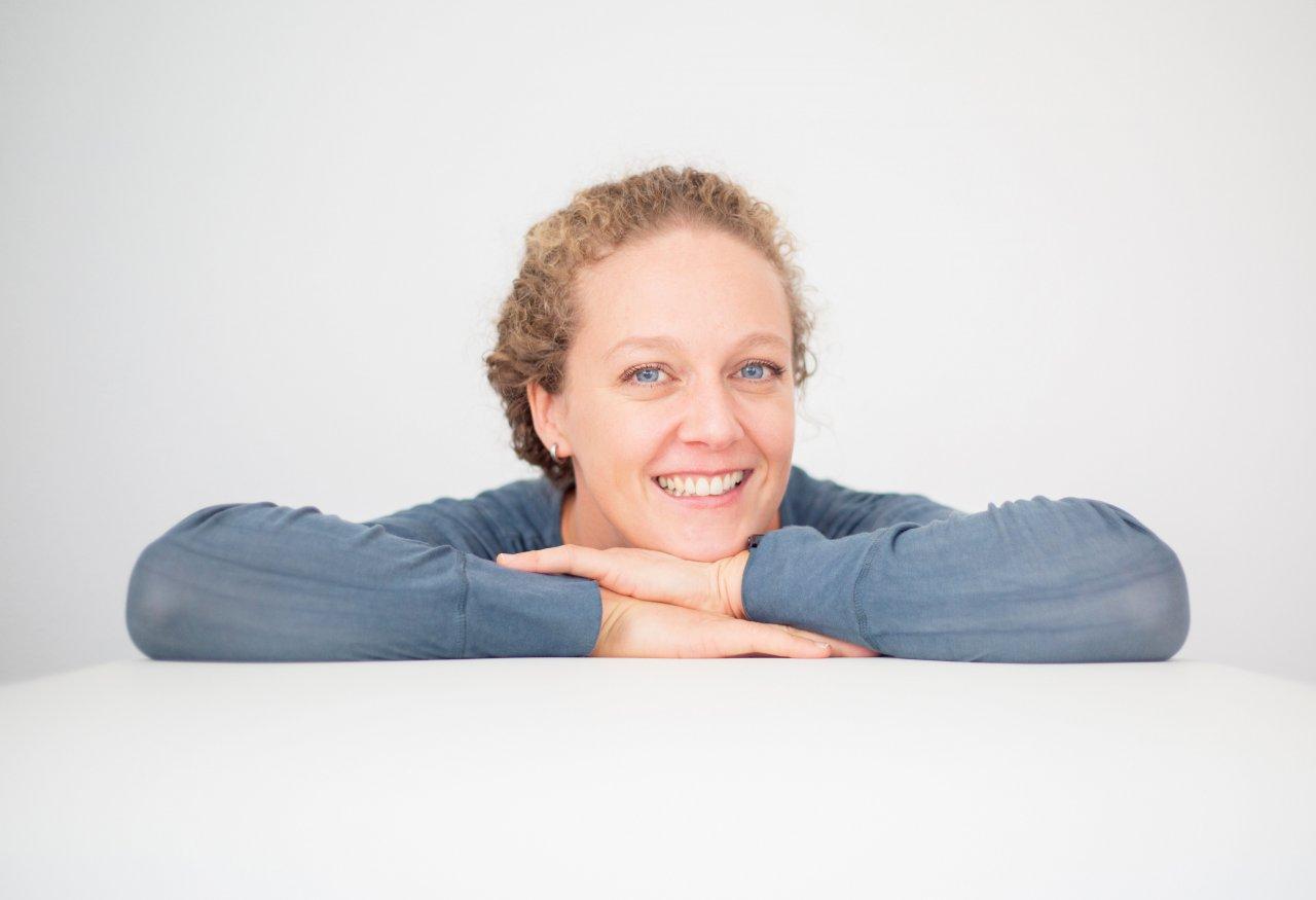 Das Foto zeigt die Heilpraktikerin Maren Klein. Sie hat ihren Kopf auf ihre Arme gelegt, die auf einem Tisch liegen. Sie trägt ihre blonden Haare zu einem Zopf und einen blauen Pullover.