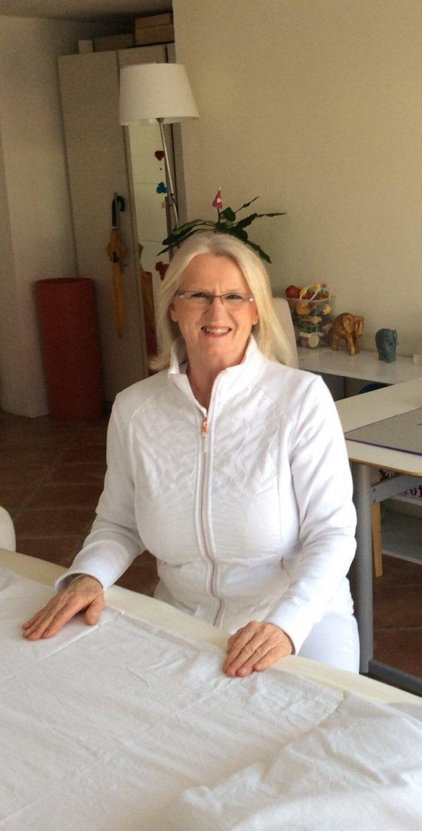 Das Foto zeigt Maria Hofer aus Leonding hinter einer Behandlungsliege sitzen. Im Hintergrund sieht man den Praxisraum. Sie hat schulterlange blonde Haare und trägt weiße Kleidung sowie eine eckige Brille.