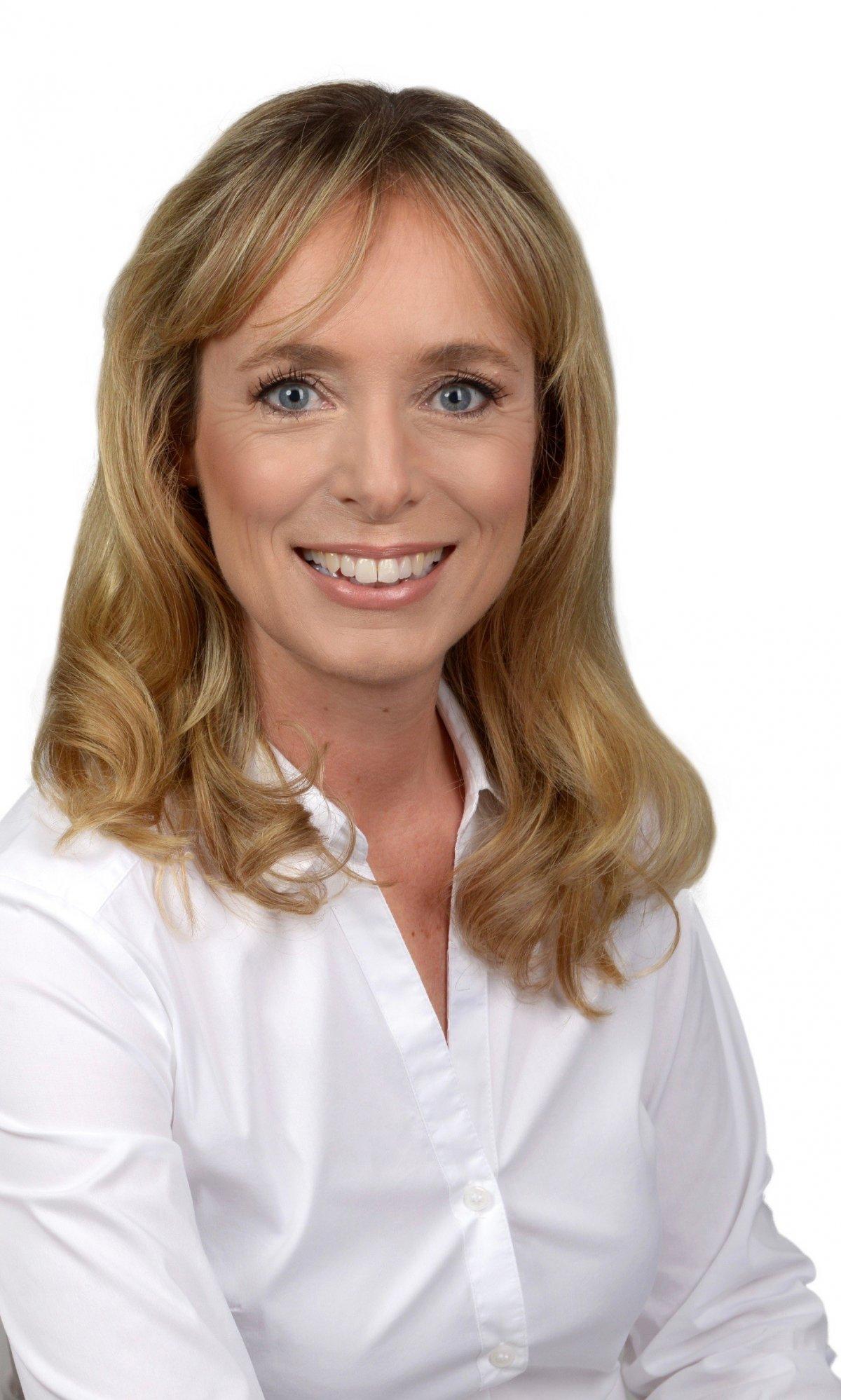 Das Foto zeigt Marie-Louise Radtke-Hendriks aus Korschenbroich vor einem weißen Hintergrund. Sie hat lange blonde Haare und einen Pony. Auf dem Foto lacht sie in die Kamera und trägt eine weiße Bluse.